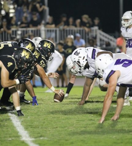 The offense line prepares to snap the ball during the fourth quarter against River Ridge. Photo by: Emma Diehl